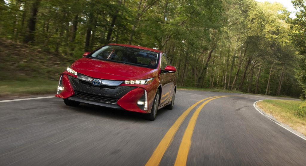 A red 2021 Toyota Prius Prime travels on a two-lane highway through sun-dappled trees