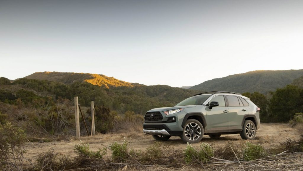 The 2021 Toyota RAV4 Adventure SUV parked on a dirt trail surrounded by grass hills. This model is recommended by Consumer Reports