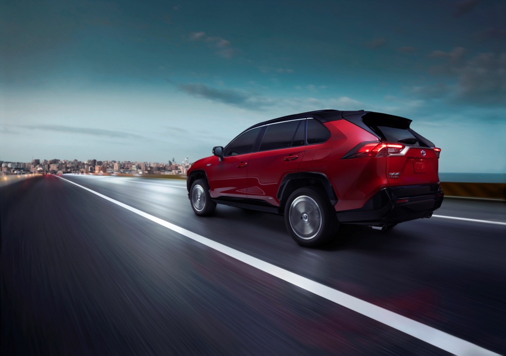 The 2021 Toyota RAV4 Prime PHEV SUV in dark red driving down a highway toward an urban city