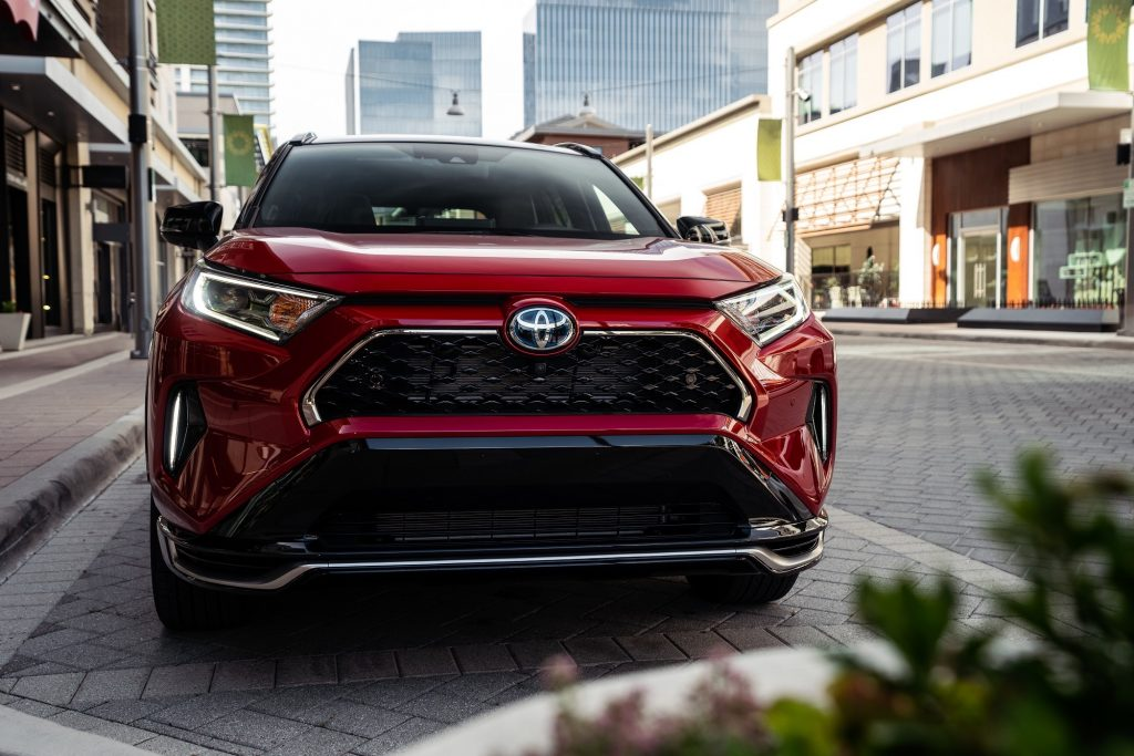 A red metallic 2021 Toyota RAV4 Prime XSE plug-in hybrid compact SUV parked on a brick road in a city