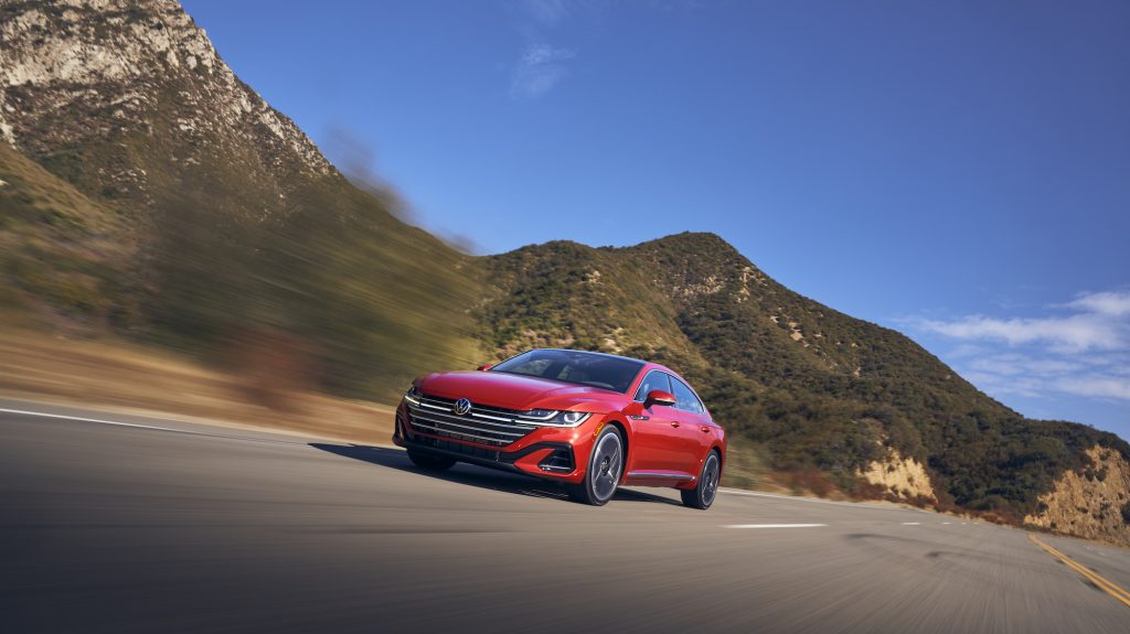 A red 2021 Volkswagen Arteon travels on a highway through mountains
