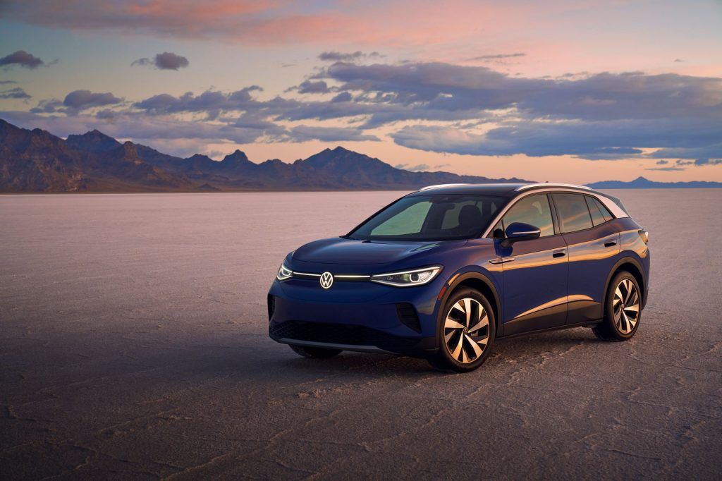 The 2021 Volkswagen ID.4 Pro S EV SUV model parked on a barren plain near mountains and a setting sun