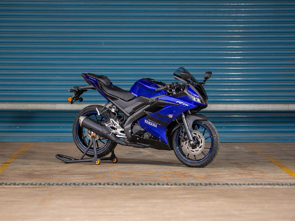 A blue-and-black 2021 Yamaha YZF-R15 on a rear-wheel stand by a turquoise garage
