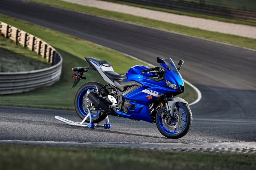 A blue-and-black 2021 Yamaha YZF-R3 sportbike parked on a racetrack on a rear-wheel stand