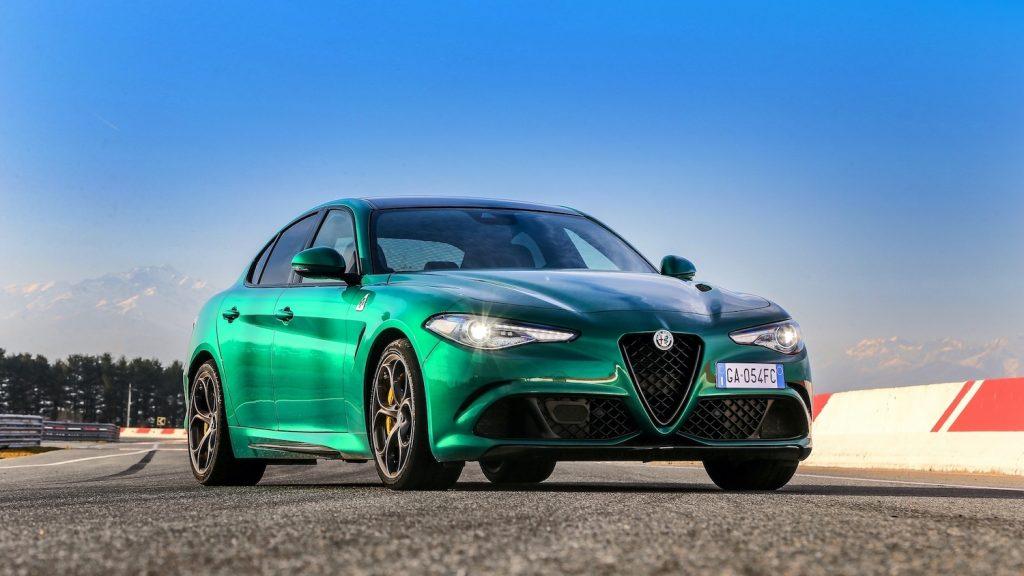 Press photo of a green Alfa Romeo Giulia Quadrifoglione on a race track, one of Car and Driver's most beautiful sedans of 2021