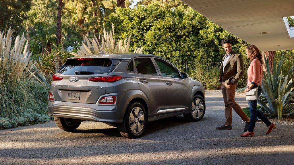 A couple walks toward a beige 2021 Hyundai Kona Electric.
