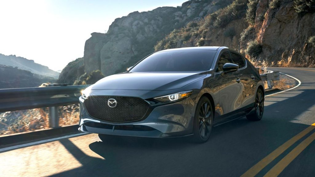 Press photo of a gray 2021 Mazda3 sedan driving a mountain road, one of Car and Driver's most beautiful sedans of 2021