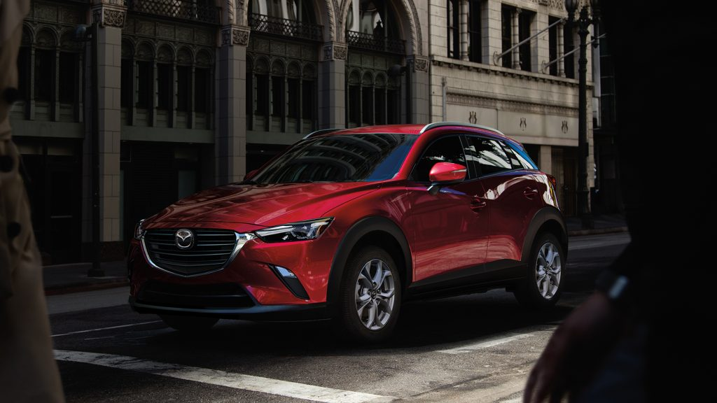 A red 2021 Mazda CX-3 at a stop line. The Mazda CX-3 is one of the cheapest SUVs you can buy.