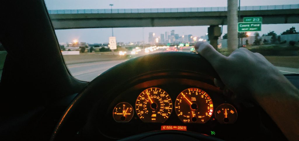The amber gauge cluster of a 2004 BMW M3 at dusk with the city in the background