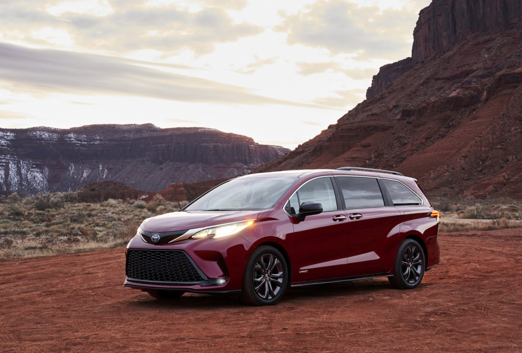A red 2021 Toyota Sienna parked in the wild on a cloudy day