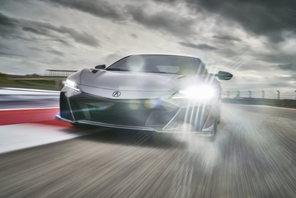 A silver 2022 Acura NSX Type S supercar travels on a racetrack under a cloudy sky