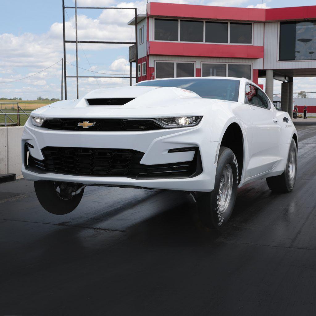 A white 2022 Chevrolet COPO Camaro wheelies down a dragstrip