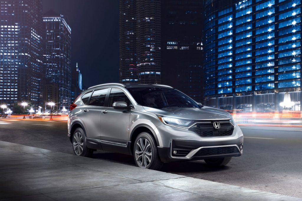 The 2022 Honda CR-V Touring SUV parked on the side of a city street at night