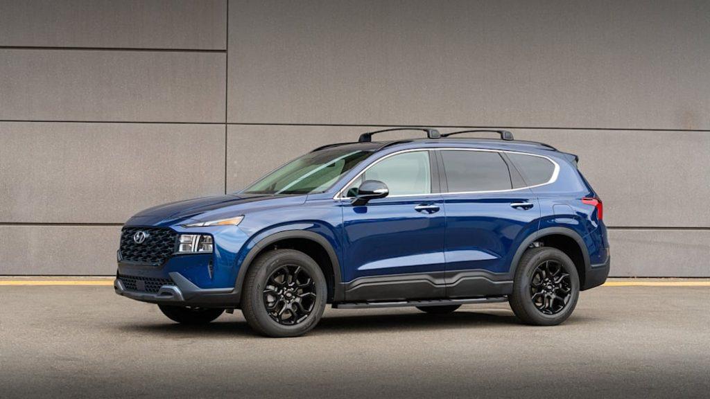 A blue 2022 Hyundai Santa Fe XRT parked near a building