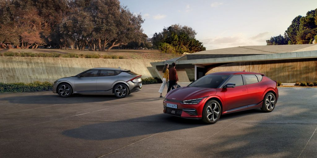 2022 Kia EV6 models in silver and red parked as a couple walks past