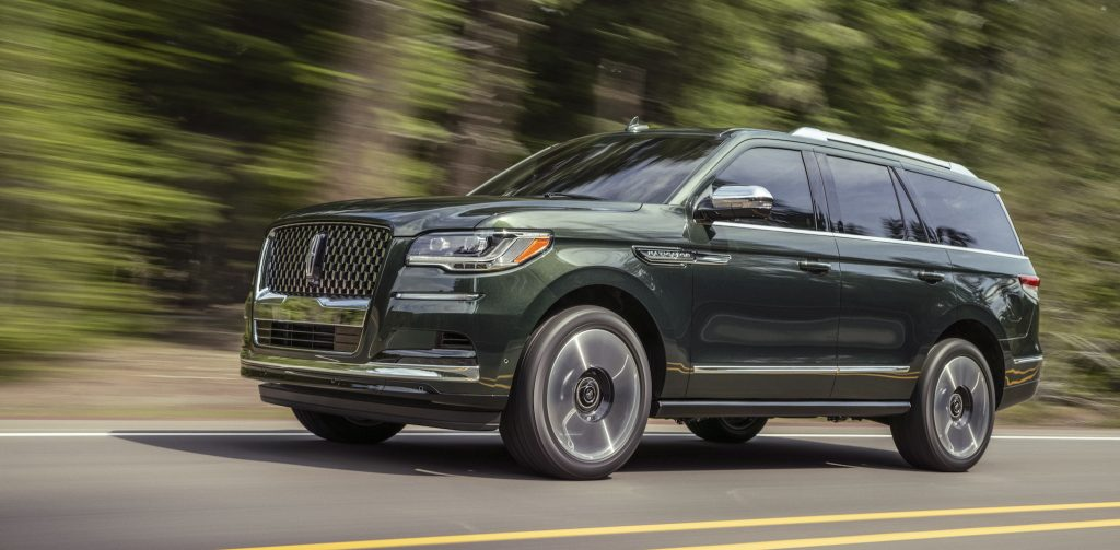 A 2022 Lincoln Navigator Manhattan Green Black Label traveling on a two-lane highway passing a blur of trees