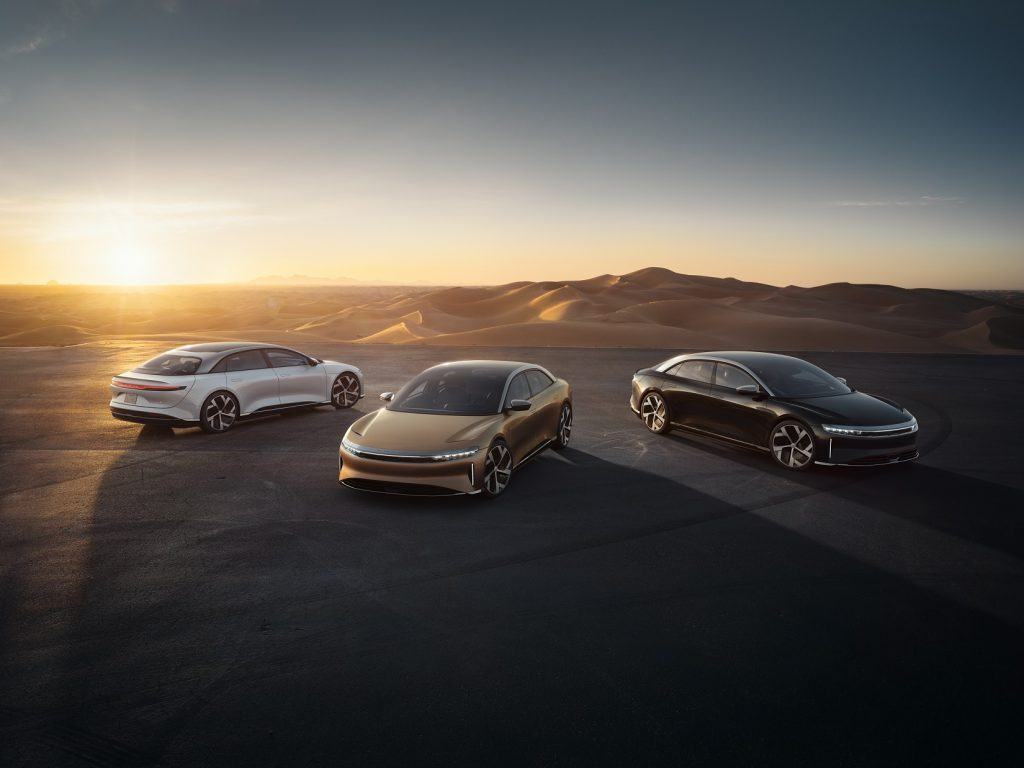 A white, gold, and brown 2022 Lucid Air parked next to a desert