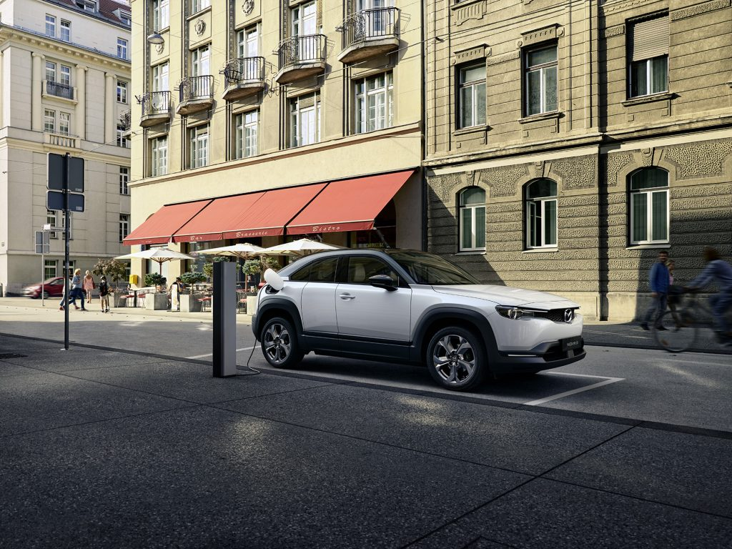 The 2022 Mazda MX-30 EV parked and charging at a charging station