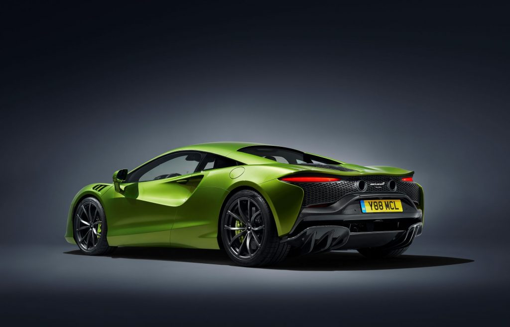 A lime green 2022 McLaren Artura in a black room with a white spotlight on the car.
