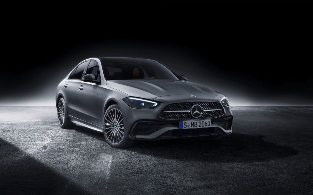 A silver 2022 Mercedes-Benz C-Class on a concrete slab with a black background.