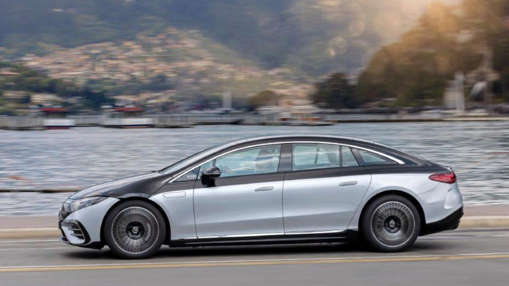 The 2022 Mercedes-Benz EQS electric sedan driving on a highway near docks