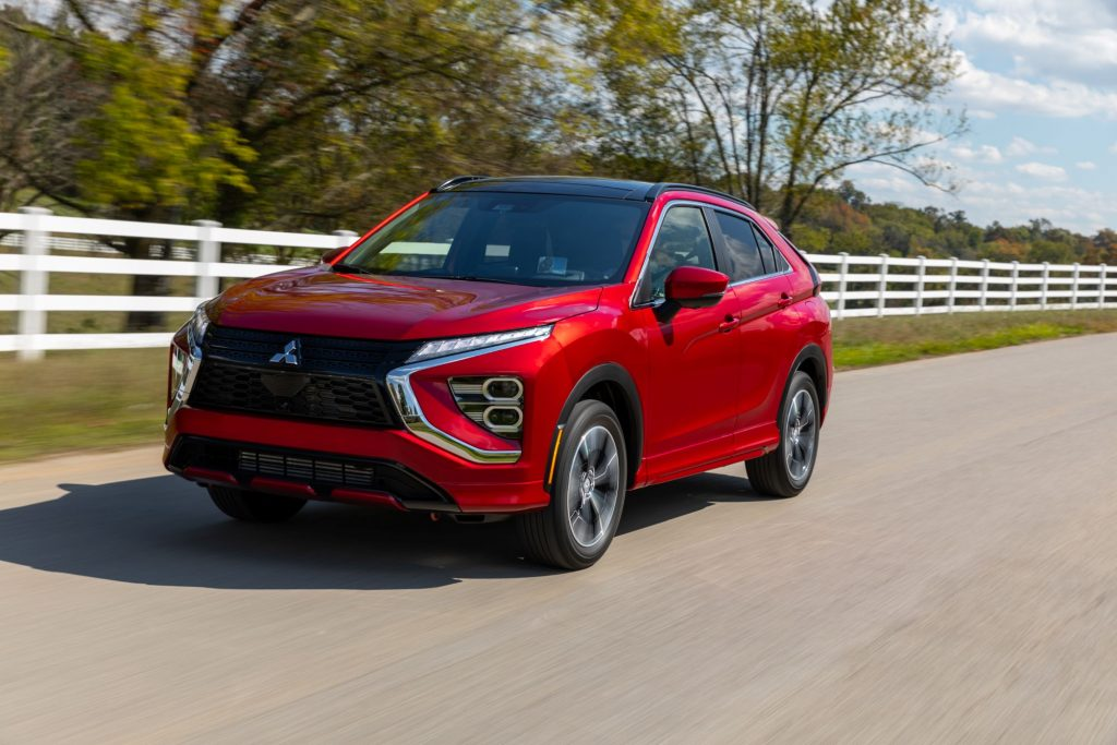 A red 2022 Mitsubishi Eclipse Cross compact SUV model driving by a white fence