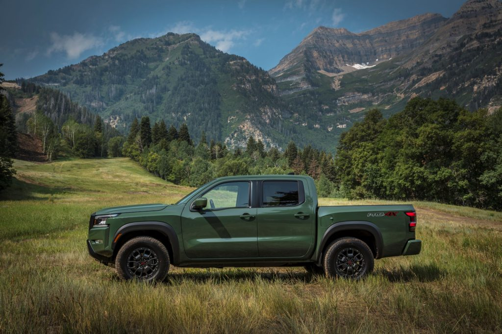 The 2022 Nissan Frontier pickup truck in green parked in a grass field near forests and mountains