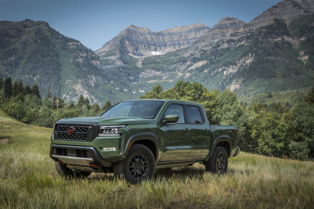 A green 2022 Nissan Frontier parked in front of the mountains
