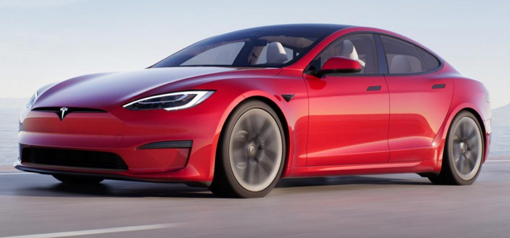 A red 2022 Tesla Model S Plaid driving down a road