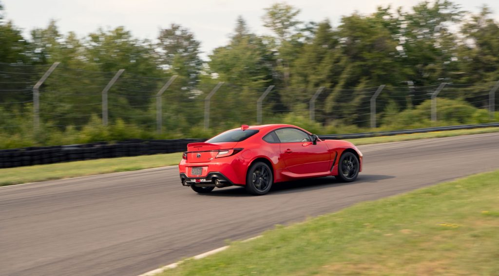 The rear 3/4 view of a red 2022 Toyota GR 86 Premium going around a racetrack corner