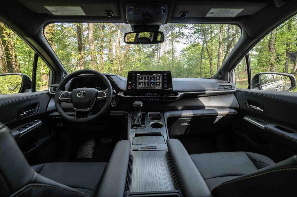 A view of the black front seats, steering wheel, dashboard, and touchscreen of a 2022 Toyota Sienna Woodland Special Edition minivan