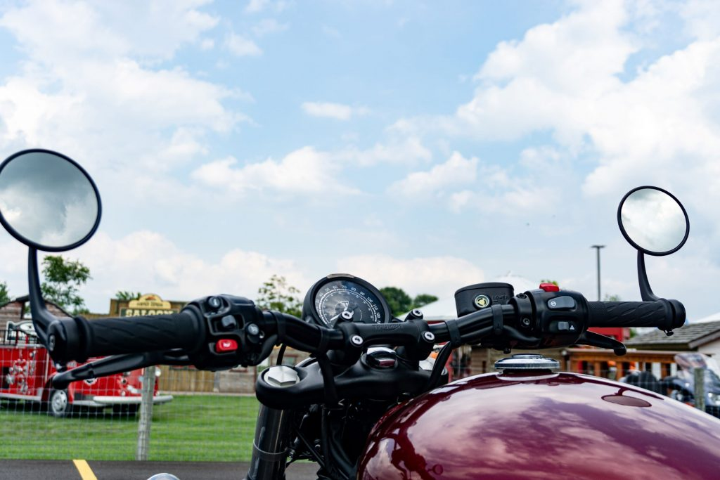The handlebars and gauge of a red 2022 Triumph Bonneville Bobber