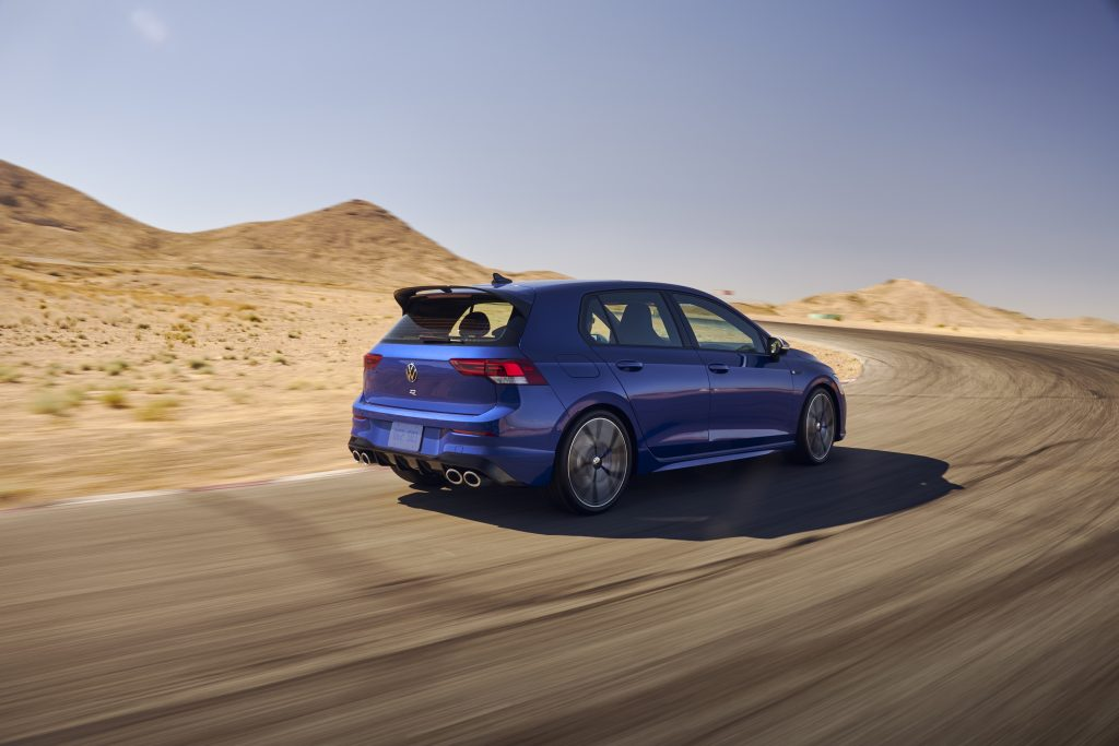 Passenger's side rear view of blue 2022 Volkswagen Golf R driving on a curvy road at speed