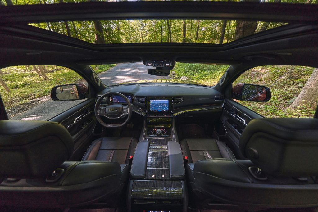 The Nappa-leather-upholstered front seats and dashboard of a 2022 Wagoneer with a sunroof parked in a forest