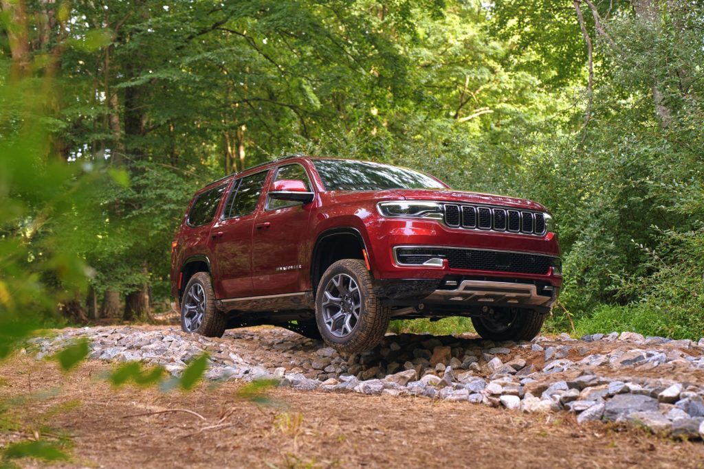 A red 2022 Wagoneer with Advanced All-Terrain Group off-roading through the forest