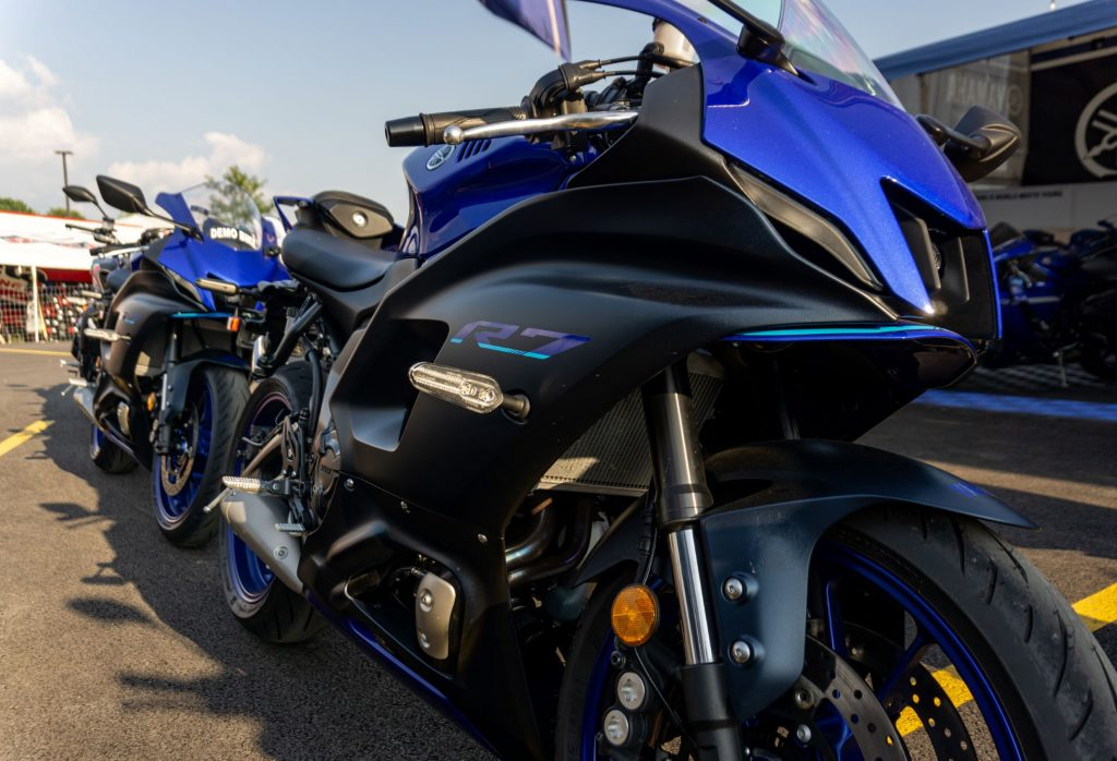 The front 3/4 view of a blue-and-black 2022 Yamaha YZF-R7 in front of another R7