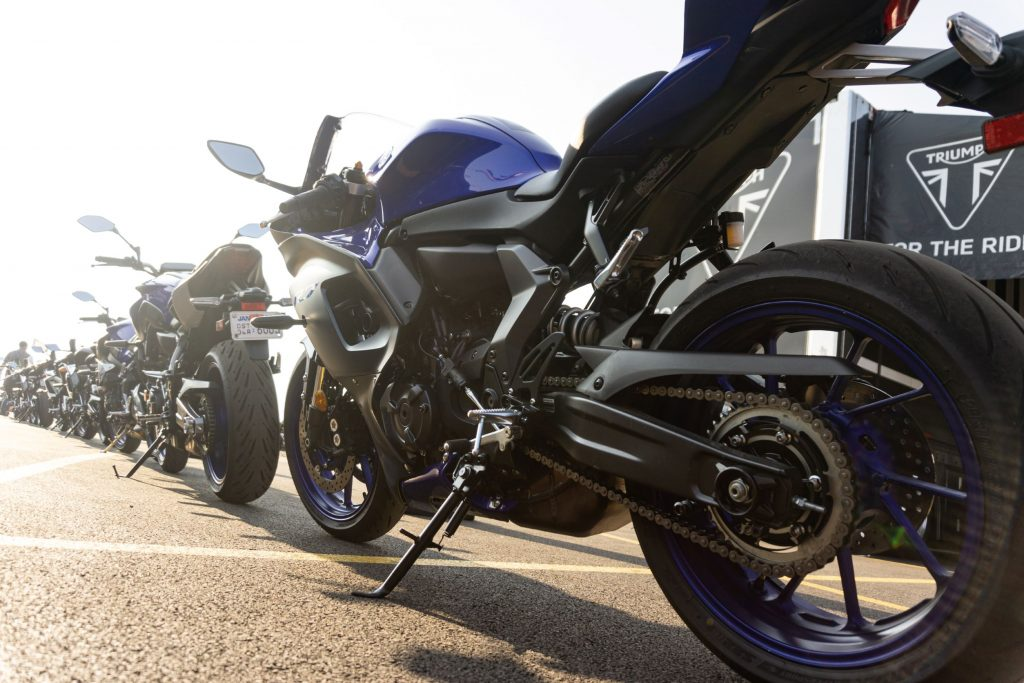 A low-angle rear 3/4 view of a blue-and-black 2022 Yamaha YZF-R7 behind a line of other bikes