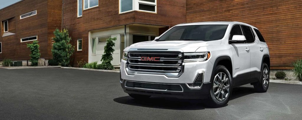 A white 2021 GMC Acadia in front of a brick house.