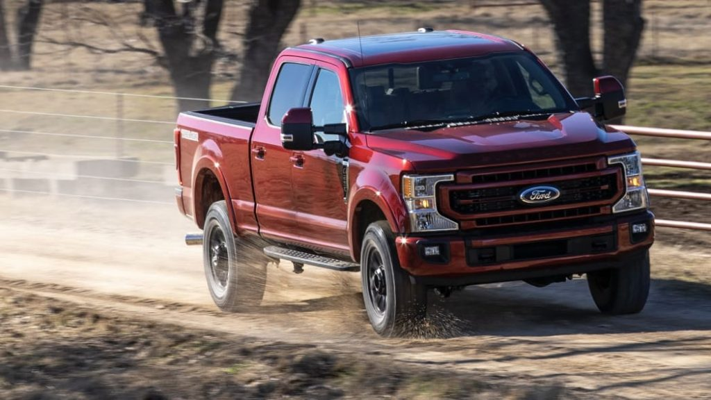 A red 2022 Ford F-250 Super Duty on a dirt road