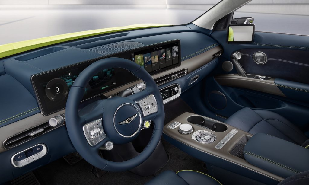The dark-blue front seats and dashboard of a chartreuse 2023 Genesis GV60 electric crossover SUV
