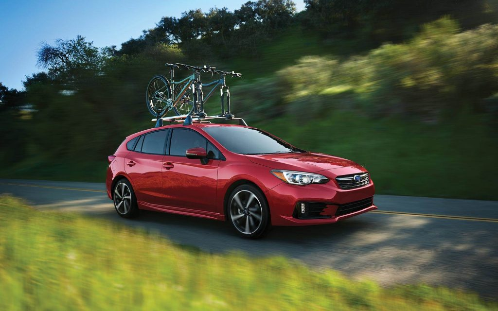 A red 2022 Subaru Impreza driving with bicycles on top. The Impreza is one of the cheapest cars you can buy.