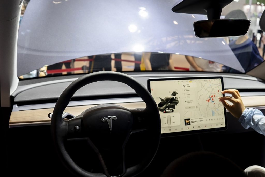 The interior of a Tesla, with steering wheel and screen.