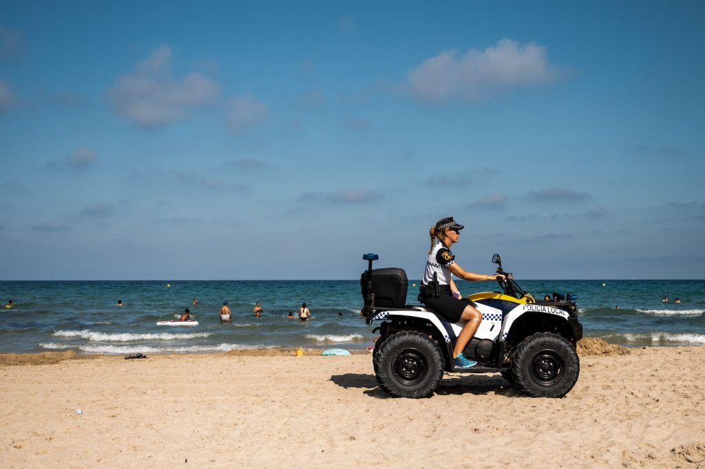 A police officer patrols on an ATV as tourists enjoy a day at the beach
