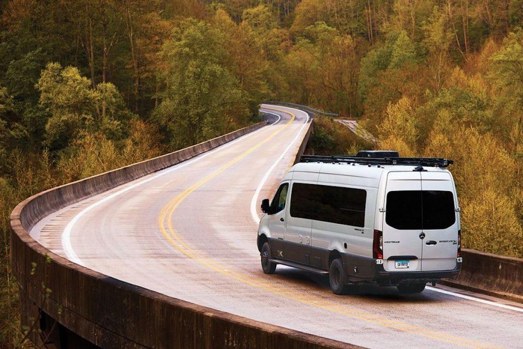 Airstream camper van driving down the road