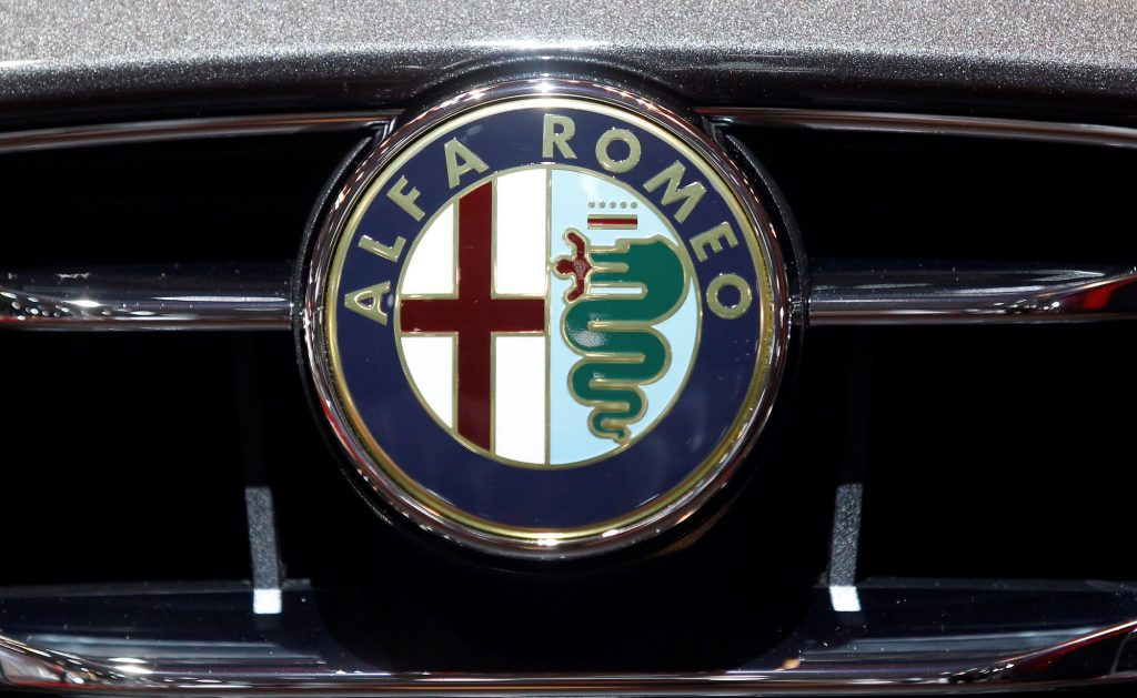 The Alfa Romeo logo on the grill of a silver car.