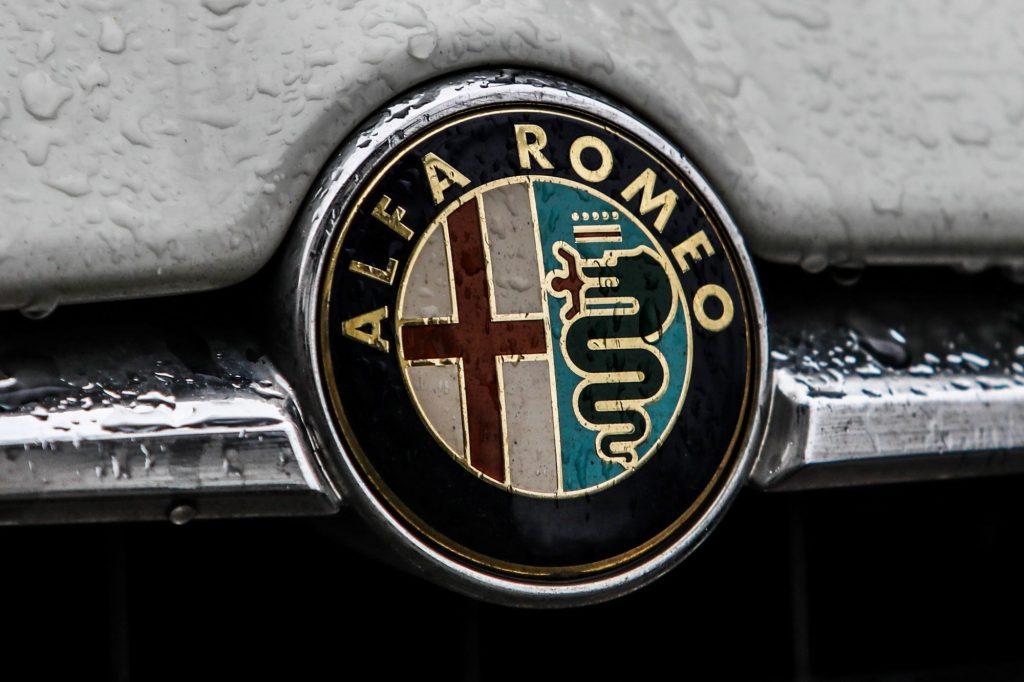Alfa Romeo logo on a grey car with rain drops.