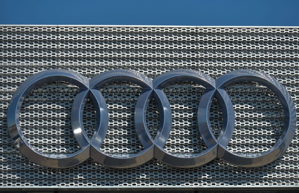 Chrome Audi logo on a mesh grille looking background.