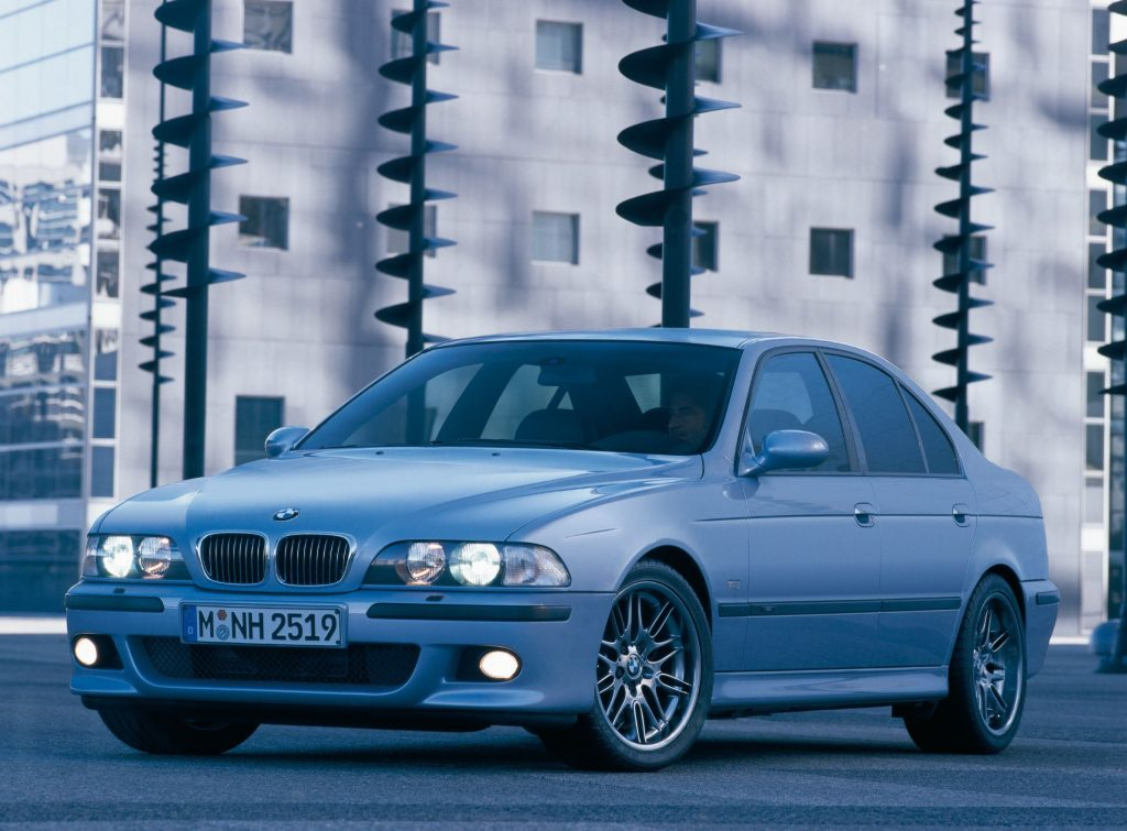 A silver BMW E39 M5 on a city street