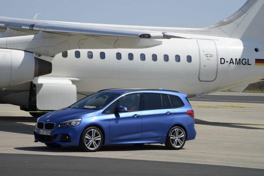 BMW minivan parked next to a plane