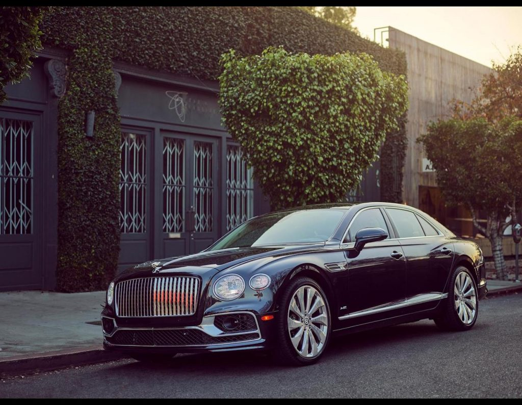 Press photo of a black 2021 Bentley Flying Spur parked on the street, one of Car and Driver's most beautiful sedans of 2021